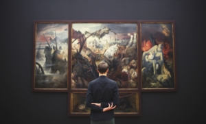 man looking at painting in art museum