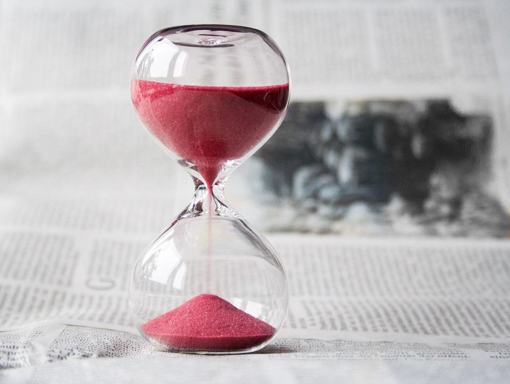 Sand timer on a newspaper